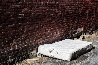 old and dirty mattress left on the side of the street